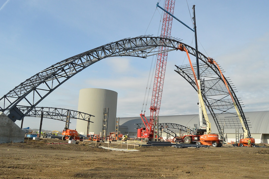DAYTON, Ohio -- Construction crews attach the keystone into place between the steel archways. The 224,000 square foot building, which is scheduled to open to the public in 2016, is being privately financed by the Air Force Museum Foundation, a non-profit organization chartered to assist in the development and expansion of the museum's facilities. (U.S. Air Force photo)