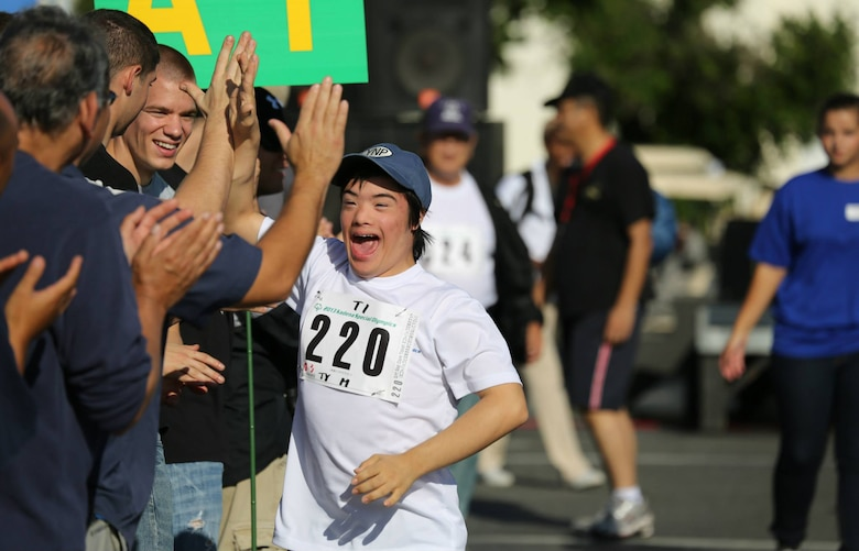 Ty Murdock, Kadena 10th grade High School student, runs a 30-meter dash during the Kadena Special Olympics on Kadena Air Base, Japan, Nov. 2, 2013. Murdock will be competing again this year in the KSO, making this his 12th consecutive year. He enjoys the applause and cheering from the crowd when he races and the competition. (Courtesy photo by Gordon Murdock)