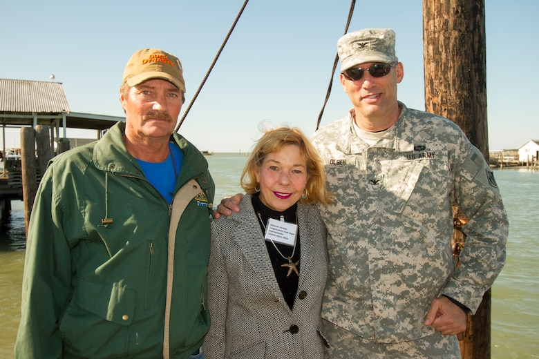 "TANGIER, Va. – Mayor James ""Ooker"" Eskridge; Deborah Christie, from Congressman Scott Rigell's office; and Col. Paul Olsen, Norfolk District commander stand along the federal navigation channel where a new jetty will be constructed protecting the boats and shacks in the harbor from damaging wave attack during coastal storms."