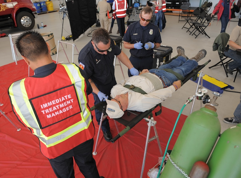 Paramedics from the Pima County Rural/Metro Fire Department treat a simulated victim during a Natural Disaster Medical System exercise at Davis-Monthan Air Force Base, Ariz., Nov. 5, 2014. D-M would be the primary patient reception site in southern Arizona in the event of a real-world natural disaster response. (U.S. Air Force photo by Airman 1st Class Chris Drzazgowski/Released)