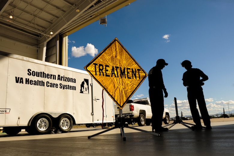 Firefighters from Golder Ranch Fire District and Tucson Airport Authority Fire Department assemble medical care signs a part of a triage area at Davis-Monthan Air Force Base, Ariz., Nov. 4, 2014. The triage area was set up in conjunction with a simulated response to a natural disaster on the Gulf Coast requiring patients to be flown to Ariz., to receive treatment. (U.S. Air Force photo by Airman 1st Class Chris Drzazgowski/Released)