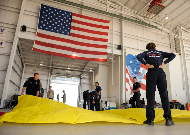 Firefighters from multiple agencies in Tucson, Ariz., construct a triage area in a hangar at Davis-Monthan Air Force Base, Ariz., Nov. 4, 2014. The triage area is part of a simulated response to a natural disaster involving the partnership of D-M, local emergency response agencies and the Southern Arizona Veterans Affairs Health Care System. (U.S. Air Force photo by Airman 1st Class Chris Drzazgowski/Released)