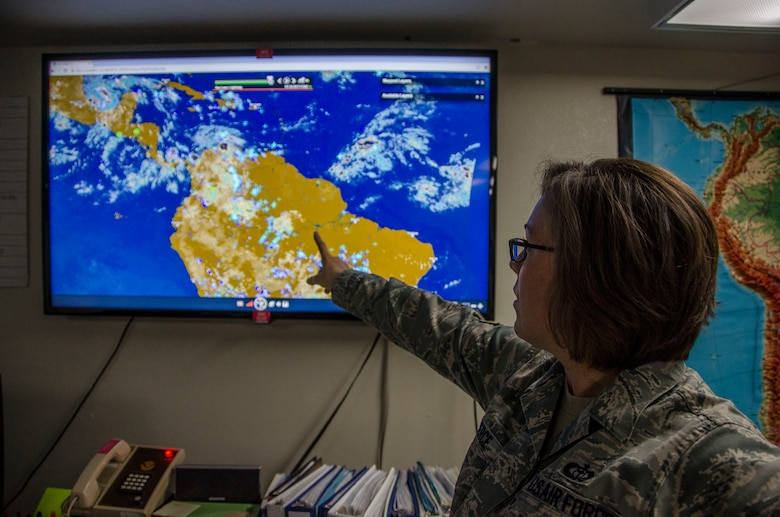 Staff Sgt. Toni Pierce, 612th Support Squadron Weather Forecaster, points to areas in South America that have the possibility of thunder storms at Davis-Monthan AFB, Ariz., Oct. 20, 2014. Members of the weather flight also issues weather watches, warnings and advisories protecting personnel and assets across a 15.6 million square mile radius. (U.S. Air Force photo by Staff Sgt. Adam Grant/Released)
