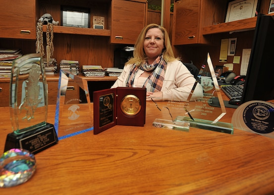 Shirley Lawson, 319th Contracting Flight contract specialist, poses with several awards she has won on six different military bases on Nov. 6, 2014. Lawson was named the Grand Forks AFB Warrior of the Week for the first week of November 2014. (U.S. Air Force photo/Senior Airman Xavier Navarro)