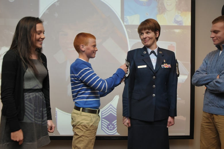Newly promoted Chief Master Sgt. Jacqueline Sweet-McNeill gets pinned by her son, Nolan, as daughter, Olivia, and eldest son, Ryan, look on during a promotion ceremony at Stratton Air National Guard Base, New York, on Nov. 2, 2014. Sweet-McNeill is the 109th Medical Group superintendent. (U.S. Air National Guard photo by Tech. Sgt. Catharine Schmidt/Released)