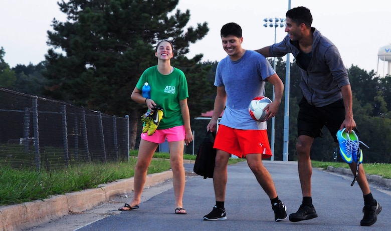 Airman 1st Class Emily Jordan, Staff Sgt. Alan Esqueda, and Senior Airman Carlos Desio, all members of the Sporting Whiteman varsity soccer team, share a laugh after practicing at Whiteman Air Force Base, Sept. 20, 2014. Sporting Whiteman routinely plays competitively against various semi-pro and collegiate teams in the region. (U.S. Air Force photo by Staff Sgt. Nick Wilson/Released)
