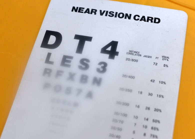 A near-vision card that tests visual acuity rests on a table at the optometry booth at 52nd Medical Group Fall Harvest Health Fair Nov. 5, 2014.  The blurred spot in the middle of the image is from a lens that simulates macular degeneration, a deterioration of the eye thought to be due by aging. The symptoms are usually blurriness in the center of vision with the peripherals unaffected. (U.S. Air Force photo by Staff Sgt. Daryl Knee/Released)