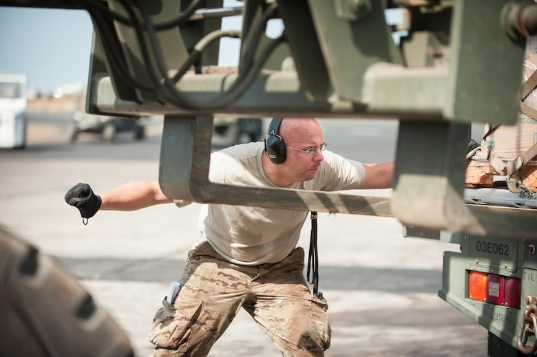 U.S. Air Force Tech. Sgt. Jarrod Blanford, an aerial porter from the Kentucky Air National Guard's 123rd Contingency Response Group, directs the placement of a pallet of humanitarian cargo from an all-terrain forklift onto a Halverston Loader at Léopold Sédar Senghor International Airport in Dakar, Senegal, Nov. 4, 2014. The cargo will then be transferred to a U.S. Air Force C-130 aircraft from Dyess Air Force Base, Texas, for delivery to Monrovia, Liberia, in support of Operation United Assistance, the U.S. Agency for International Development-led, whole-of-government effort to contain the Ebola virus outbreak in West Africa. (U.S. Air National Guard photo by Maj. Dale Greer)