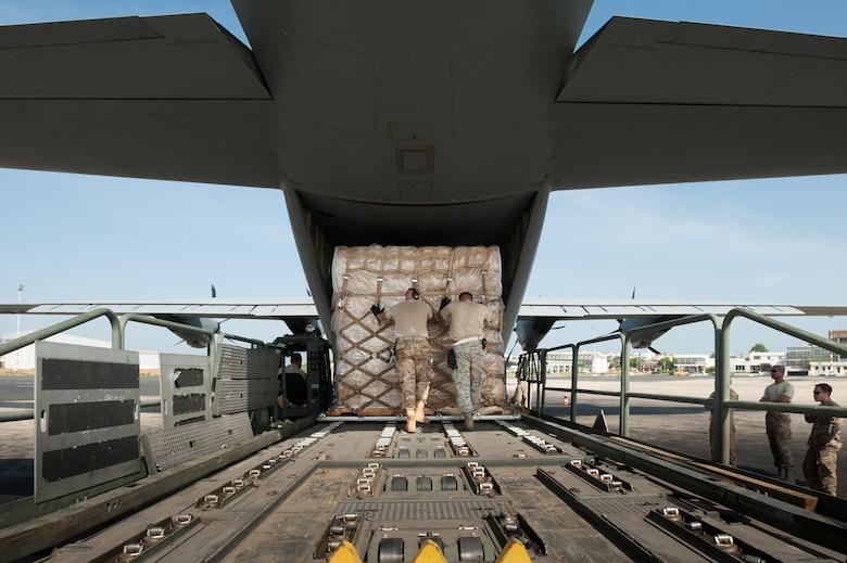 Aerial porters from the Kentucky Air National Guard's 123rd Contingency Response Group push a pallet of cargo onto a C-130 aircraft from Dyess Air Force Base, Texas, at Léopold Sédar Senghor International Airport in Dakar, Senegal, Nov. 4, 2014. The Kentucky Airmen are operating an Aerial Port of Debarkation to funnel humanitarian aid to Liberia in support of Operation United Assistance, the U.S. Agency for International Development-led, whole-of-government effort to contain the Ebola virus outbreak in West Africa. (U.S. Air National Guard photo by Maj. Dale Greer)