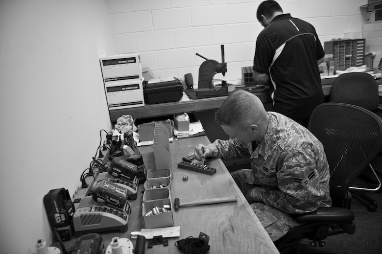 Airman 1st Class Andrew Conner, 1st Special Operations Civil Engineer Squadron structural apprentice, and David Console, 1st SOCES locksmith, work on locks at the locksmith shop on Hurlburt Field, Fla., Nov. 6, 2014. The locksmith shop provides keys to Hurlburt units, and fixes and maintains locks throughout the base. (U.S. Air Force photo/Senior Airman Krystal M. Garrett)