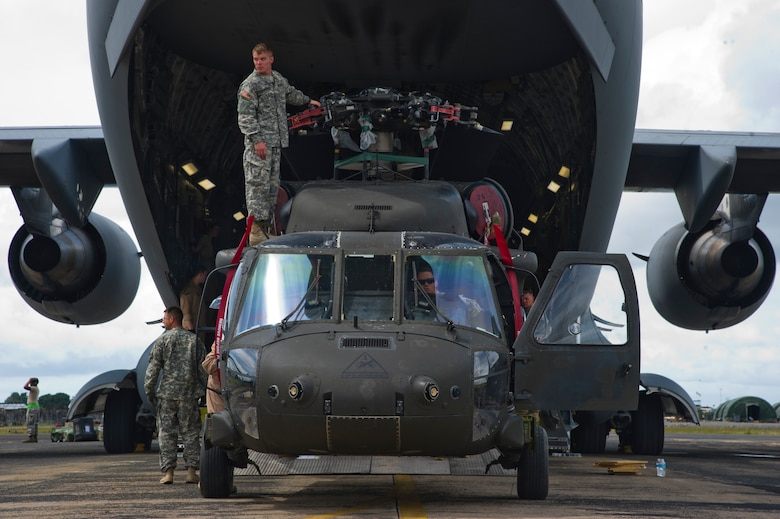 Service members unload a U.S. Army UH-60 Black Hawk from a U.S. Air Force C-17 Globemaster III Oct. 30, 2014, during Operation United Assistance. The U.S. Africa Command-led operation provides command and control, logistics, training and engineering support to the U.S. government's efforts to contain the Ebola virus outbreak in West African nations. (U.S. Air Force photo/Staff Sgt. Gustavo Gonzalez)