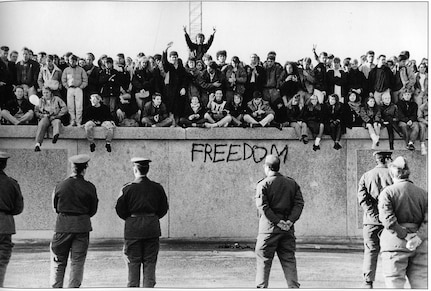 In November, 1989, East German students sit atop the Berlin Wall at the Brandenburg Gate in front of border guards. The destruction of the once-hated wall signaled the end of a divided Germany.