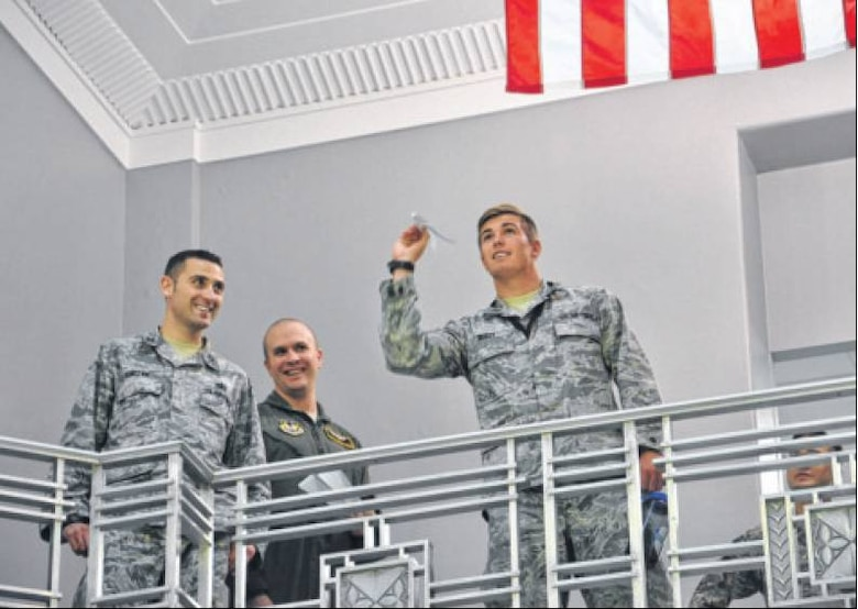 (From left) Capt. Daniel Luczak of the Air Force Life Cycle Management Center (AFLCMC) and Master Sgt. Matthew Weede of Air Force Materiel Command look on as 2nd Lt. Max Reilly of AFLCMC prepares to launch his paper airplane during a fundraiser for the Miami Valley Combined Federal Campaign on Oct. 29 in the rotunda of Bldg. 12, home of AFLCMC's Agile Combat Support Directorate, the contest's sponsor. (Air Force photos by Diane Kofoed)