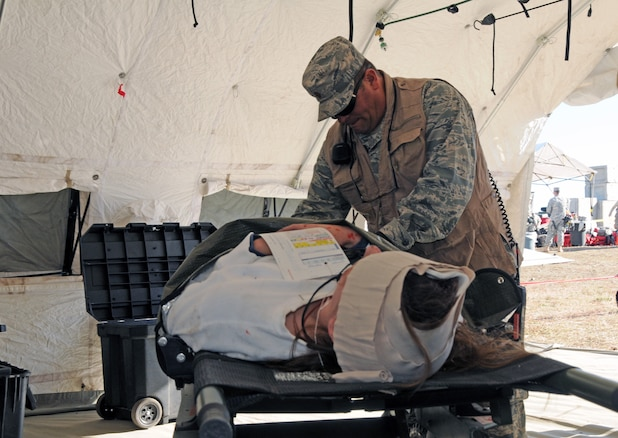 Maj. Todd Bingham, CERFP chief nurse with the 151st Medical Group, treats a mock casualty during Vigilant Guard training at a simulated rubble pile in Magna, Utah on November 4, 2014. (Air National Guard photo by Staff Sgt. Annie Edwards/RELEASED)