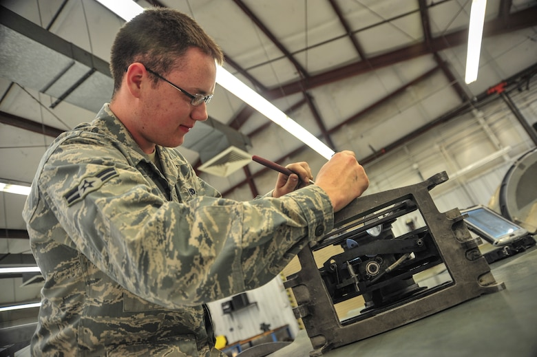 U.S. Air Force Airman 1st Class Mason Roberts, 355th Equipment Maintenance Squadron weapons armament technician, inspects a tension equalizer at Davis-Monthan Air Force Base, Ariz., Nov. 6, 2014.  The tension equalizer ensures the slack in the 30 mm GAU-8/A Gatling gun system remains constant while firing.  (U.S. Air Force Photo by Airman 1st Class Chris Massey/Released)