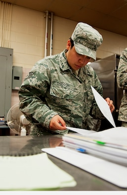 Staff Sgt. Angelica Chacon, 8th Medical Group noncommissioned officer in charge of force health, looks over inspection sheets during a health inspection at the O'Malley Dining Facility Sept. 12, 2014, at Kunsan Air Base, Republic of Korea.  Chacon was recognized by the 8 MDG as their pride of the pack outstanding performer and got a chance to show Wolf and Wolf Chief how she contributes to the Wolf Pack mission. (U.S. Air Force photo by Senior Airman Divine Cox)