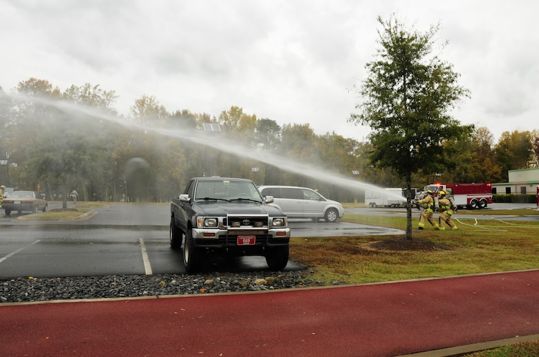 U.S. Air Force Staff SSgt's Brian Campbell and Joseph Upchurch, firefighters for the 145th Civil Engineer Squadron, use a high pressure fire hose to simulate putting out a fire during the 145th Airlift Wing's annual Anti-Terrorism Exercise simulating a car bomb detonation inside the perimeter of the North Carolina Air National Guard Base, Charlotte Douglas Intl. Airport, Nov. 1, 2014. The exercise initiated force protection measures across the base and tested the Wing's ability to respond accordingly. (U.S. Air National Guard photo by Senior Airman Laura J. Montgomery, 145th Public Affairs/Released)