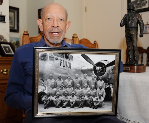 Arthur Hicks, a former Tuskegee Airman, poses with a photo of his graduating class from pilot training, Nov. 7, 2014, Vandenberg Air Force Base, Calif. Veterans Day is a nationally celebrated holiday that honors those who have served in the United States Armed Forces. (U.S. Air Force photo by Airman Robert J. Volio/Released)