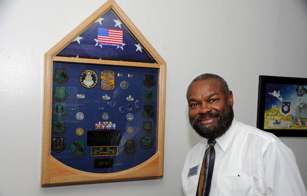 Calvin Tucker, 30th Force Support Squadron chief of sustainment services flight, poses next to his shadow box containing his military accomplishments, Nov. 7, 2014, Vandenberg Air Force Base, Calif. Veterans Day is a nationally celebrated holiday that honors those who have served in the United States Armed Forces. (U.S. Air Force photo by Airman Robert J. Volio/Released)