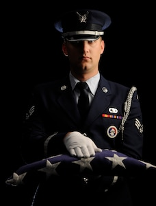 A Joint Base Andrews Honor Guardsman poses for a photo Nov. 07. 2014. The American flag is presented as it is during funerals for deceased military vetarans when passing the flag to the next-of-kin. (U.S. Air Force photo/SSgt Nichelle Anderson)