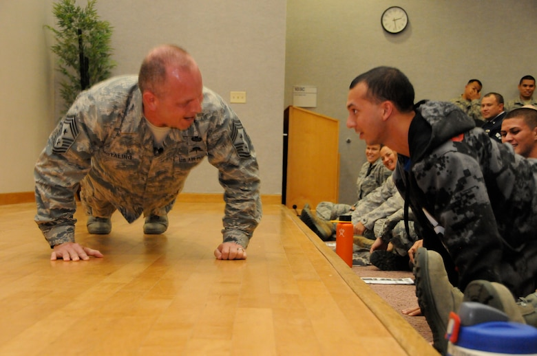 U.S. Air Force Chief Master Sgt. James W. Hotaling, command chief master sergeant of the Air National Guard, performs push-ups with newly recruited Kaimana Mattson, Hawaii Air National Guard, during a Town Hall Meeting at Joint Base Pearl Harbor Hickam on Nov. 9, 2014. Mattson is a prospective recruit for the 203rd Air Refueling Squadron in student flight and is awaiting orders for Basic Military Training. (U.S. Air National Guard photo by Airman 1st Class Robert Cabuco)