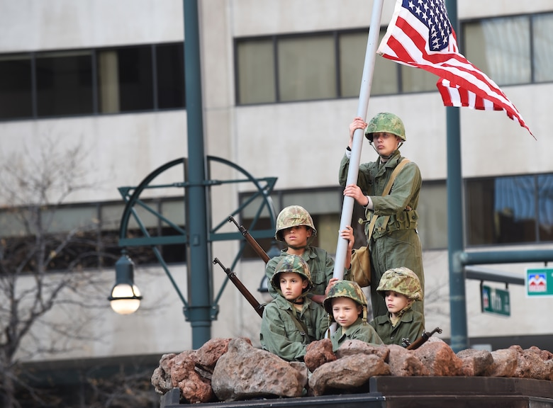 A group of boys re-enact the photo of the American flag being raised on Iwo Jima during the Veteran's Day Parade, hosted by the Colorado Veterans Project, Nov. 8, 2014, in Denver. The parade consisted of more than 75 groups honoring American veterans by highlighting each American war, beginning with the Revolutionary War and ending with Operation Iraqi Freedom. (U.S. Air Force photo by Airman 1st Class Samantha Saulsbury/Released)