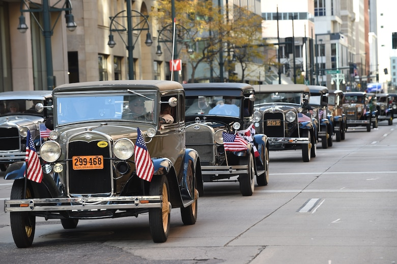A row of vintage cars driven by military veterans line the street during the Veteran's Day Parade, hosted by the Colorado Veterans Project, Nov. 8, 2014, in Denver. The parade consisted of more than 75 groups honoring American veterans by highlighting each American war, beginning with the Revolutionary War and ending with Operation Iraqi Freedom. (U.S. Air Force photo by Airman 1st Class Samantha Saulsbury/Released)