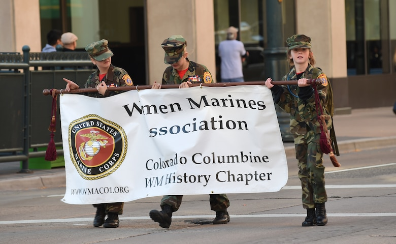 A group of girls hold a Women Marines Association banner during the Veteran's Day Parade, hosted by the Colorado Veterans Project, Nov. 8, 2014, in Denver. The parade consisted of more than 75 groups honoring American veterans by highlighting each American war, beginning with the Revolutionary War and ending with Operation Iraqi Freedom. (U.S. Air Force photo by Airman 1st Class Samantha Saulsbury/Released)