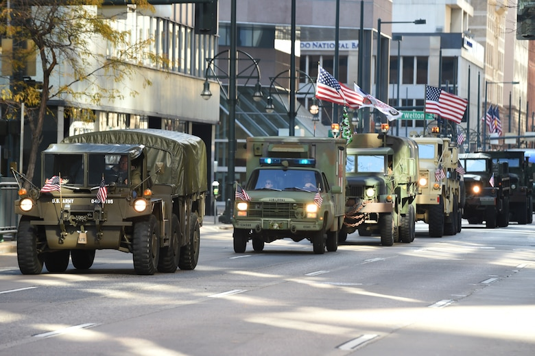 A convoy driven by military members lines the street during the Veteran's Day Parade, hosted by the Colorado Veterans Project, Nov. 8, 2014, in Denver. The parade consisted of more than 75 groups honoring American veterans by highlighting each American war, beginning with the Revolutionary War and ending with Operation Iraqi Freedom. (U.S. Air Force photo by Airman 1st Class Samantha Saulsbury/Released)