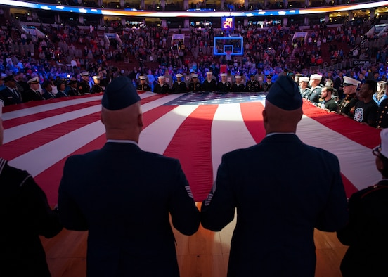 """Airmen, Soldiers, Sailors, Marines and Coast Guardsmen hold a large American flag during the singing of the """"Star Spangled Banner,"""" prior to the start of a Chicago Bulls versus Philadelphia 76ers basketball game Nov. 7, 2014, at the Wells Fargo Center, in Philadelphia. The 76ers organization provided free tickets to hundreds of service members from local military instillations, including Dover Air Force Base, Del. and Joint Base McGuire-Dix-Lakehurst, N.J. (U.S. Air Force photo/Airman 1st Class Zachary Cacicia)"""