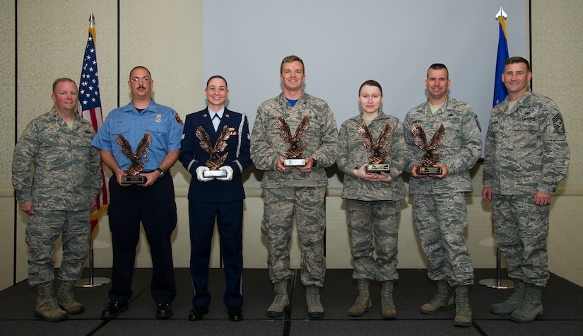 Col. Jeffrey DeVore, 628th Air Base Wing commander (left) and Chief Master Sgt. Mark Bronson, 628th Air Base Wing command chief (right), congratulate (left to right) Glen Pilger, Civilian Category I of the Quarter, Senior Airman Erin Winkler, Honor Guard Member of the Quarter, Capt. Phillip Hoyt, Company Grade Officer of the Quarter, Tech. Sgt. Lyudmila Mueller, NCO of the Quarter, and Master Sgt. Clinton Dunnehoo, Senior NCO of the Quarter during the 628th ABW quarterly awards ceremony Nov. 7, 2014, at the Charleston Club on Joint Base Charleston, S.C. The quarterly awards are held to recognize outstanding Airmen, NCOs, senior NCOs, company grade officers and civilians for their hard work and dedication. (U.S. Air Force photo/Airman 1st Class Clayton Cupit)