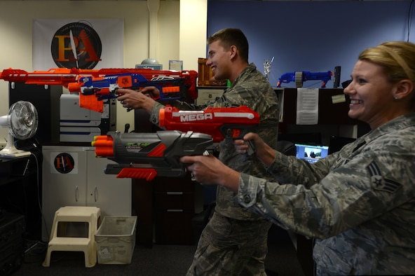 U.S. Air Force Senior Airman Tabatha Zarrella and Airman 1st Class Michael Cossaboom, 20th Fighter Wing Public Affairs photojournalists, participate in an office NERF battle Nov. 7, 2014, at Shaw Air Force Base, S.C. Maintaining the social pillar of Comprehensive Airman Fitness while in a work setting ensures personal and professional success and resiliency of the Airmen in the public affairs office. CAF's pillars of fitness include mental, physical, social, and spiritual. (U.S. Air Force photo by Airman 1st Class Jensen Stidham/Released)