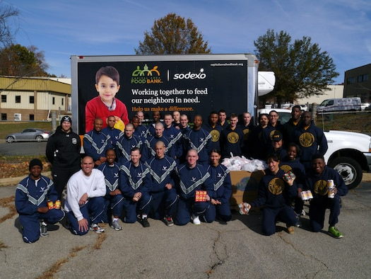 Members of the U.S, Air Force and Navy Honor Guards pose for a group photo Nov. 8, 2014, at the Capital Area Food Bank in Lorton, Va. Guardsmen from both military branches assembled 750 bags of donated food estimated to feed up to 2,800 people this Thanksgiving. (Courtesy photo/Michelle Kuzenko)