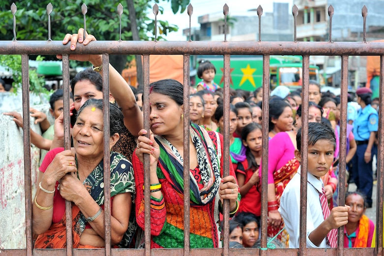 Nepalese women and children wait outside the gate to be seen by Operation Pacific Angel-Nepal at a health services outreach site in Manahari, Nepal, Sept. 9, 2014. PACANGEL supports U.S. Pacific Command's capacity-building efforts by partnering with other governments, non-governmental agencies and multilateral militaries in the respective region to provide medical, dental, optometry and engineering assistance to their citizens. (U.S. Air Force photo by Staff Sgt. Melissa B. White)