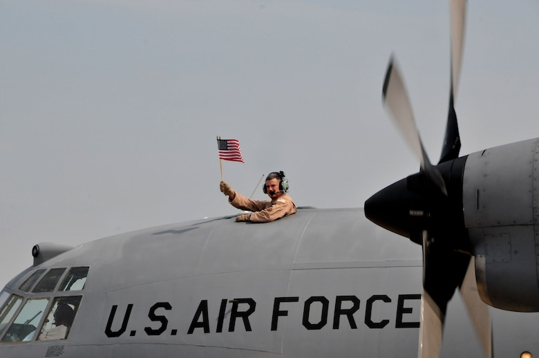 U.S. Air Force Staff Sgt. Rob Levings, Flight Engineer for the 145th Operations Support Squadron, waves an American flag, saying goodbye to family and friends as he and other airmen from the 145th Airlift Wing deploy to Southwest Asia. The C-130 Hercules aircraft departed from the North Carolina Air National Guard base, Charlotte Douglas Intl Airport, June 26, 2014. (U.S. Air National Guard photo by Master Sgt. Patricia F. Moran, 145th Public Affairs/Released)
