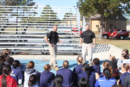 Major Brian A. Eovito (center) and Sgt. Maj. Gordon M. Miller, the top leaders for Recruiting Station Jacksonville, Florida, speak to female poolees during a pool function held at Moody Air Force Base, Georgia, Oct. 31, 2014. The young women undergoing training had the rare chance to see firsthand a drill instructor outside of recruit training.  The Command of Recruiting Station Jacksonville gathered the female poolees from its recruiting sub-stations, in order to prepare them for future endeavors as they take on the challenge of becoming Marines.  The command also had the opportunity to further evaluate the female poolees for potential assignment in previously closed combat arms Military Occupational Specialties.