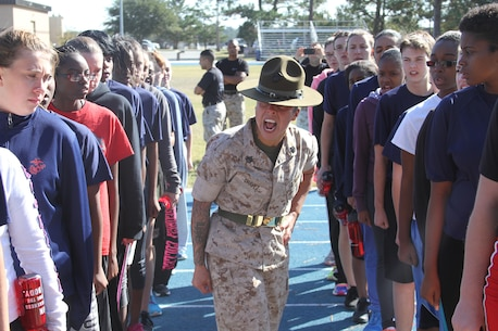 Staff Sgt. Carolin Chavez, a drill instructor at Marine Corps Recruit Depot Parris Island, South Carolina, screams commands to female poolees during a pool function at Moody Air Force Base, Georgia, Oct. 31, 2014. The young women undergoing training had the rare chance to see firsthand a drill instructor outside of recruit training. The Command of Recruiting Station Jacksonville, Florida, gathered all the female poolees from its recruiting sub-stations, in order to prepare them for future endeavors as they take on the challenge of becoming Marines. The command also had the opportunity to further evaluate the female poolees for potential assignment in previously closed combat arms Military Occupational Specialties.