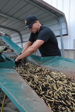 A Joint Base San Antonio-Lackland Recycling Center employee examines ammunition brass Nov. 11, 2014, as part of the base's recycling effort in San Antonio, Texas. The installation operates a zero-cost recycling program, with recycling proceeds used to pay worker salaries and the facility's operating and maintenance costs. (U.S. Air Force photo/Jennifer Schneider)