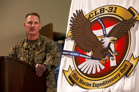 Lt. Col. Eric C. Malinowski, commanding officer of Combat Logistics Battalion 31, 31st Marine Expeditionary Unit, addresses the battalion during the unveiling of the unit's new crest Nov. 12 at Camp Hansen's West Chapel. The new design pays homage to the 31st MEU while still maintaining symbols used in previous versions. Each symbol on the crest holds a special meaning to CLB-31. Malinowski is from Portsmouth, New Hampshire. (U.S. Marine Corps photo by Lance Cpl. Tyler Ngiraswei/ Released)