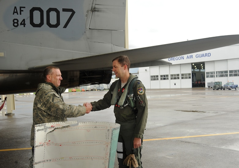 Capt. Ryan Shuck, 123rd Fighter Squadron, right, shakes hands with Master Sgt. Dean Wells, left, after returning from the test flight for Aircraft 84-007, Oct. 23, 2014, Portland Air National Guard Base, Ore. (U.S. Air National photo by Tech. Sgt. John Hughel, 142nd Fighter Wing Public Affairs)