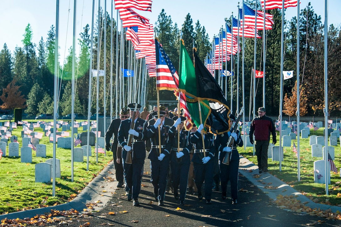 Fairchild Air Force Base's Honor Guard flanked by Airway Heights' Veterans of Foreign Wars Post 3386 and Fairchild's Boy Scout Troop 342 lead the procession of service and community members alike during a Veterans Day ceremony at Fort George Wright Veterans Cemetery, Nov. 11, 2014, in Spokane, Wash. Since its inception on May 13, 1938, Veterans Day continues to be observed on November 11, regardless of what day of week it falls. (U.S. Air Force photo/Staff Sgt. Benjamin W. Stratton)