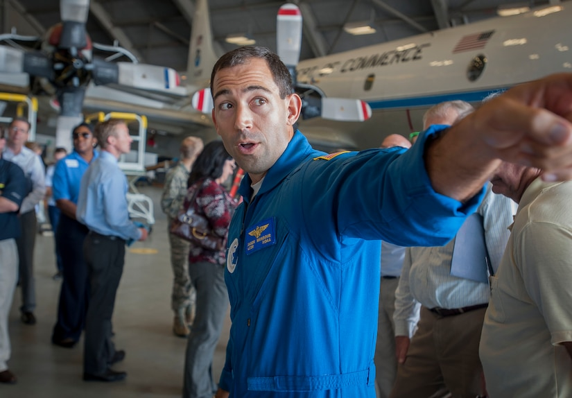 """Lt  . Cmdr. Jason Mansour, G-IV SP Hurricane Hunter pilot, speaks with a group of Joint Base Charleston civic leaders Nov. 4, 2014, inside Hangar 5 at MacDill Air Force Base, Fla. The NOAA mission includes the """"Hurricane Hunters,"""" teams of scientists who fly into hurricanes for scientific purposes. (U.S. Air Force photo/Senior Airman Tom Brading)"""