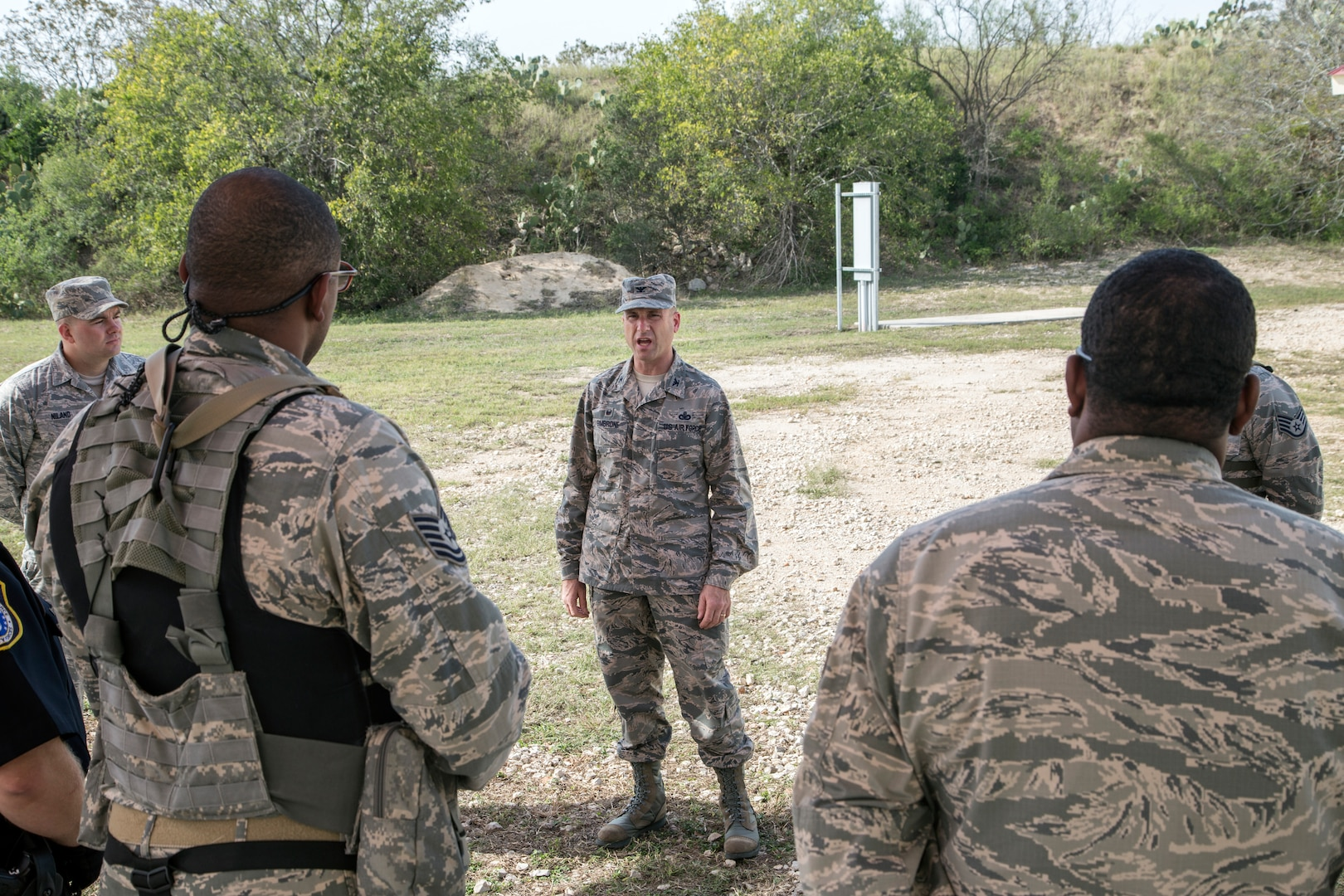 Col. Michael Gimbrone, 502nd Security Forces and Logistics Support Group commander, addresses members of the 902nd Security Forces Squadron after completing a barricaded suspect exercise Nov. 10 at Joint Base San Antonio-Randolph's Camp Talon. Security forces members exchanged simulated munitions fire with hostiles throughout the exercise, bringing more realism while practicing assault force maneuvers during the exercise scenario. (U.S. Air Force photo by Johnny Saldivar)