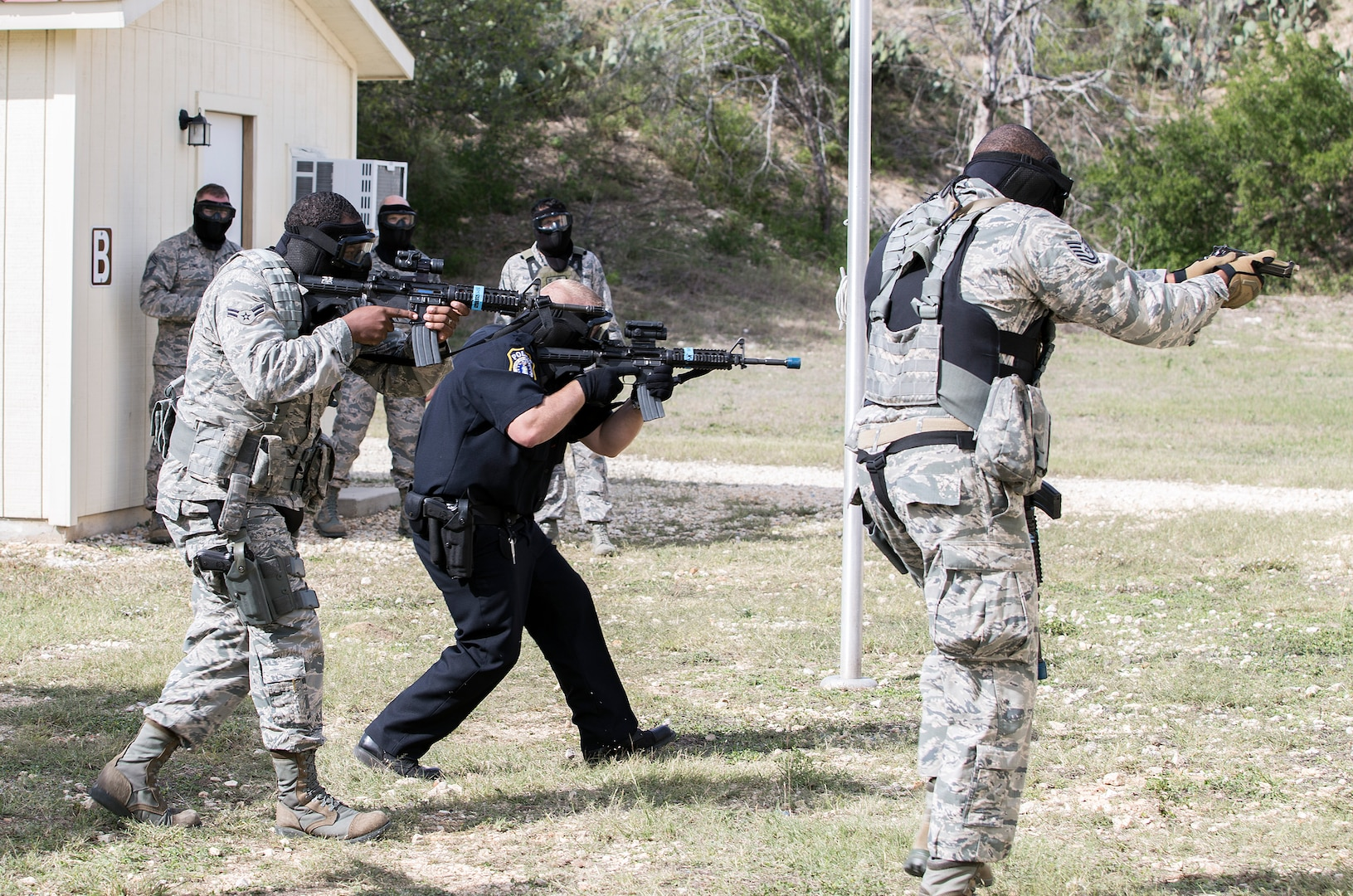 Tech. Sgt. William Graham (at right), Officer Daniel Rolin (center) and Airman 1st Class Joshua Ridgeway (at left), members of the 902nd Security Forces Squadron, push through to neutralize simulated hostile threats during a barricaded suspect exercise Nov. 10 at Joint Base San Antonio-Randolph's Camp Talon. Security forces members exchanged simulated munitions fire with hostiles throughout the exercise, bringing more realism while practicing assault force maneuvers during the exercise scenario. (U.S. Air Force photo by Johnny Saldivar)