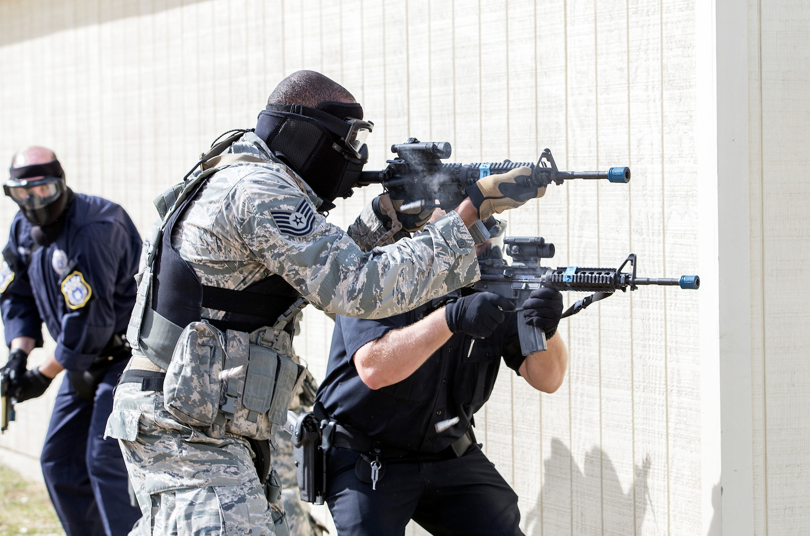 Members of the 902nd Security Forces Squadron fire at hostiles during a barricaded suspect exercise Nov. 10 at Joint Base San Antonio-Randolph's Camp Talon. Security forces members exchanged simulated munitions fire with hostiles throughout the exercise, bringing more realism while practicing assault force maneuvers during the exercise scenario. (U.S. Air Force photo by Johnny Saldivar)