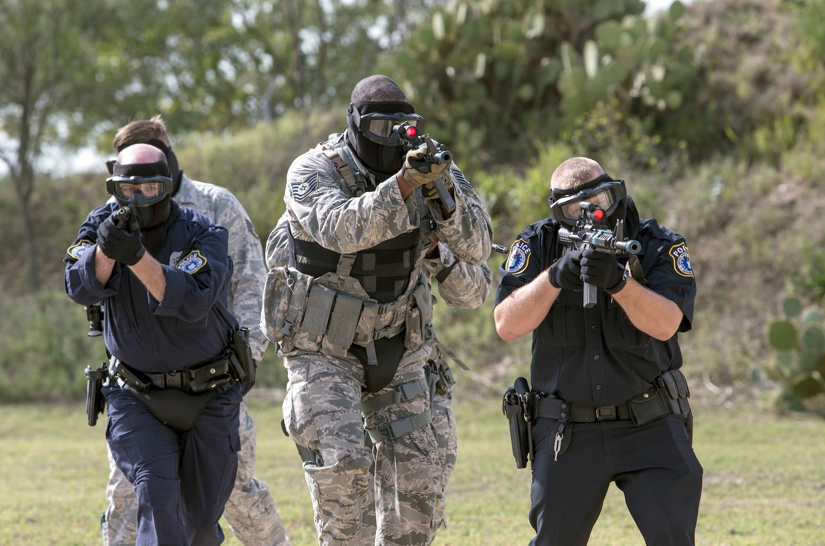 Members of the 902nd Security Forces Squadron prepare to assault in a file formation during a barricaded suspect exercise Nov. 10 at Joint Base San Antonio-Randolph's Camp Talon. Security forces members exchanged simulated munitions fire with hostiles throughout the exercise, bringing more realism while practicing assault force maneuvers during the exercise scenario. (U.S. Air Force photo by Johnny Saldivar)