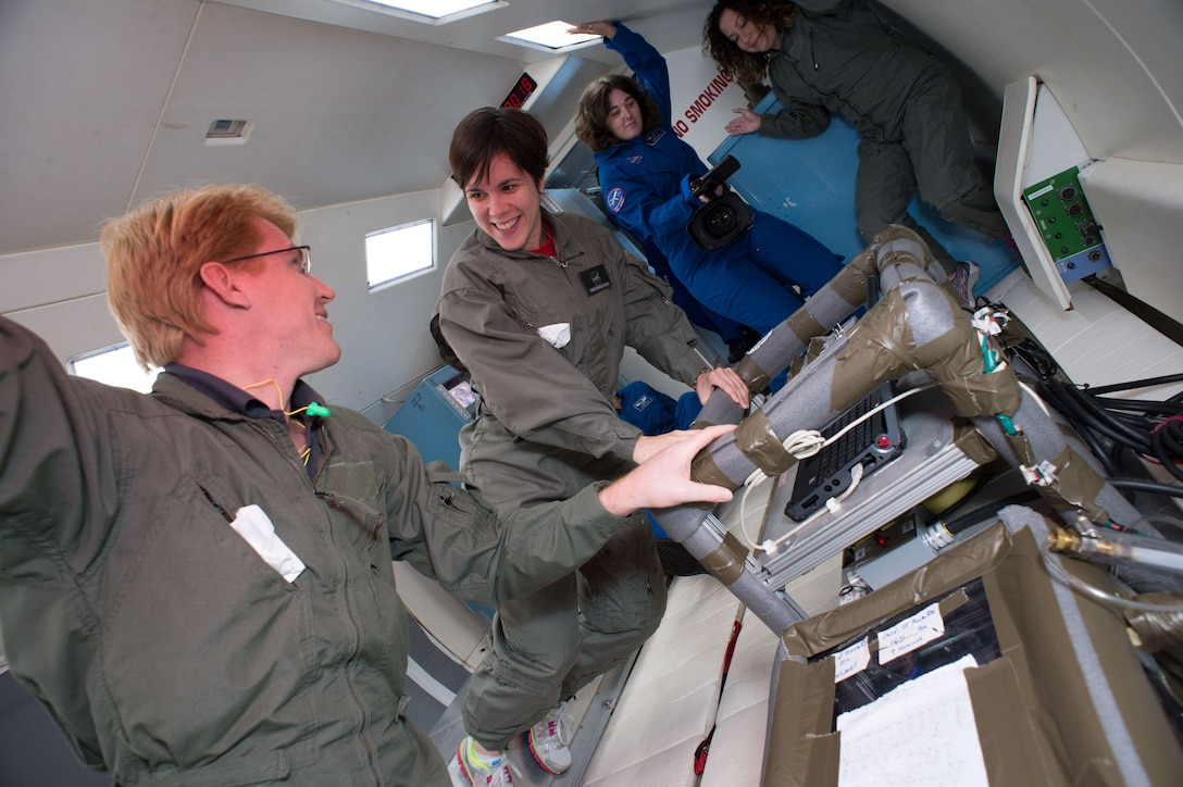 """Dr. Craig Priest, (far left), Senior Research Fellow at the University of South Australia, experiences microgravity in NASA's """"Weightless Wonder"""" research aircraft.  Priest was on board to test new Australian developed micro-structured electrodes for use in fuel-cell technologies. His collaboration with NASA evolved from his participation in several interagency meetings co-organized by the Air Force Office of Scientific Research and intended to develop and foster S&T relationships with Australian principal investigators. As a result of these same meetings, one of Priest's students will soon be conducting research for a NASA center located at the University of Puerto Rico as part of a new international exchange program. (Photo courtesy of NASA.)"""