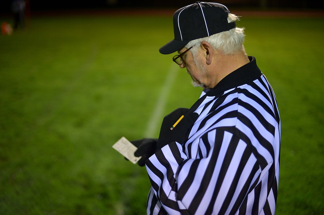 A football referee reviews his scorecard during the intramural football championship game at Spangdahlem Air Base, Germany, Nov. 10, 2014. After calling several timeouts, the 52nd Communications Squadron battled back and forth against the 52nd Civil Engineer Squadron, pushing them into overtime. (U.S. Air Force photo by Airman 1st Class Kyle Gese/Released)