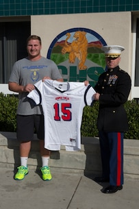 Kyle Hoppe, offensive center for Chaparral High School receives his Semper Fidelis All-American Bowl jersey from Maj. Brian Donlon, commanding officer of Marine Corps Recruiting Station San Diego in the weight room in front of his fellow football players at Chaparral High School, Nov. 13, 2014. Hoppe is among approximately 100 student athletes from across the nation selected to participate in the game at the StubHub Center in Carson, Calif., Jan. 4, 2015.