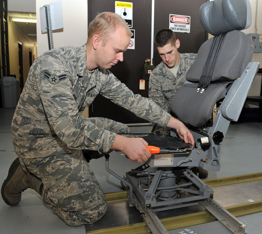 Airmen 1st Class Joseph Hall and Austin Bridges practice replacing a cracked seat pan on a missile combat crew operator's chair Oct. 31, 2014, in their new Survivable Systems Team work center at Malstrom Air Force Base, Mont. Before SST was formed, repairs at launch control centers were scheduled around maintenance tasks at launch facilities and often considered low priority jobs. The SST is a new team created through Air Force Global Strike Command's Force Improvement Program to focus primarily on LCC maintenance. Hall and Bridges are 341st Maintenance Group SST members. (U.S. Air Force photo/John Turner)
